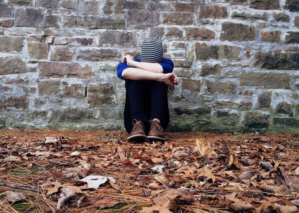 image of someone looking alone, ashamed, sad, useless.