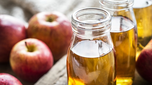 Photo of apples and a jar of apple cider vinegar: apple cider vinegar is the best to use when making bone broth for dogs