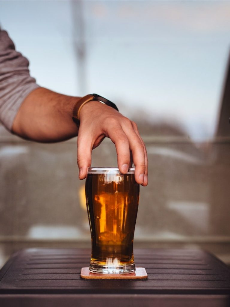 an image of a hand with a glass of beer