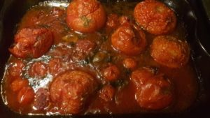 Photo of tomatoes, wine, garlic and herbs in an oven tray after baking, ready to make the most incredible soup
