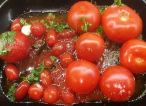 tomatoes, wine, garlic and herbs in an oven tray to make soup